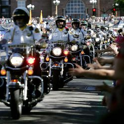 The Salt Lake County sheriffs' motor unit gets close to the crowd to give high fives during the Days of '47 Parade in Salt Lake City Saturday.