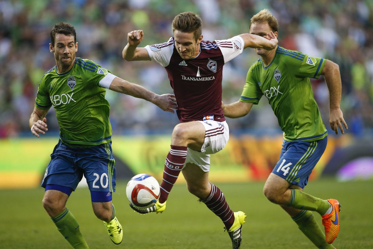 Colorado Rapids forward Kevin Doyle (9) gets a touch in between Seattle Sounders FC defender Zach Scott (20) and defender Chad Marshall (14) for a goal during the second half at CenturyLink.