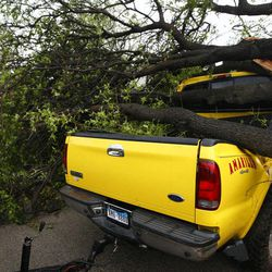 """Harold Widner clears a fallen tree from his truck in Arlington, Texas on Tuesday, April 3, 2012.  Several reported tornadoes tore through the Dallas area on Tuesday, tossing semis in the air and leaving crumpled tractor trailers strewn along highways and in truck stop parking lots.   The National Weather Service reported at least two separate """"large and extremely dangerous"""" tornadoes south of Dallas and Fort Worth."""