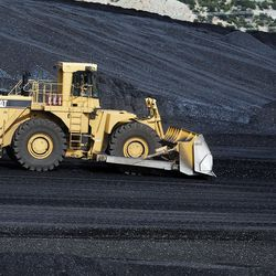 A loader pushes coal at the Huntington power plant in Huntington on Tuesday, March 24, 2015.