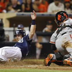 San Diego Padres' Logan Forsythe beats the attempted tag by San Francisco Giants catcher Buster Posey while scoring on a hit by Yasmani Grandal during the fifth inning of a baseball game Saturday, Sept. 29, 2012, in San Diego.