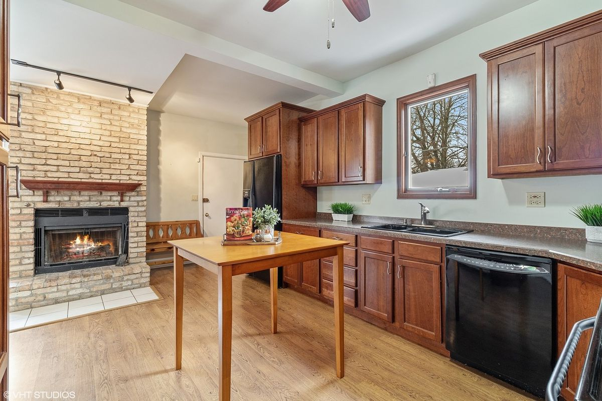 A kitchen with dark wooden cabinets and a brick fireplace.