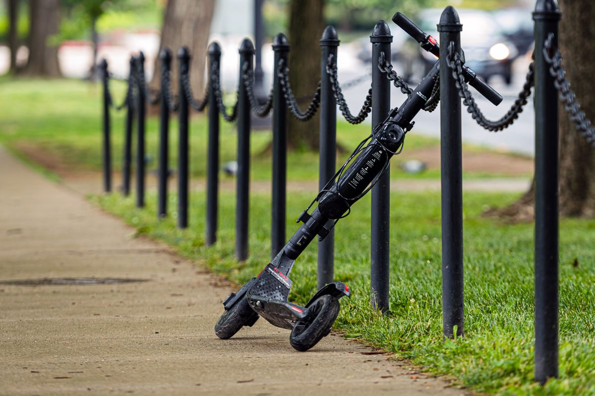 An electric scooter is seen leaning on a chained fence.