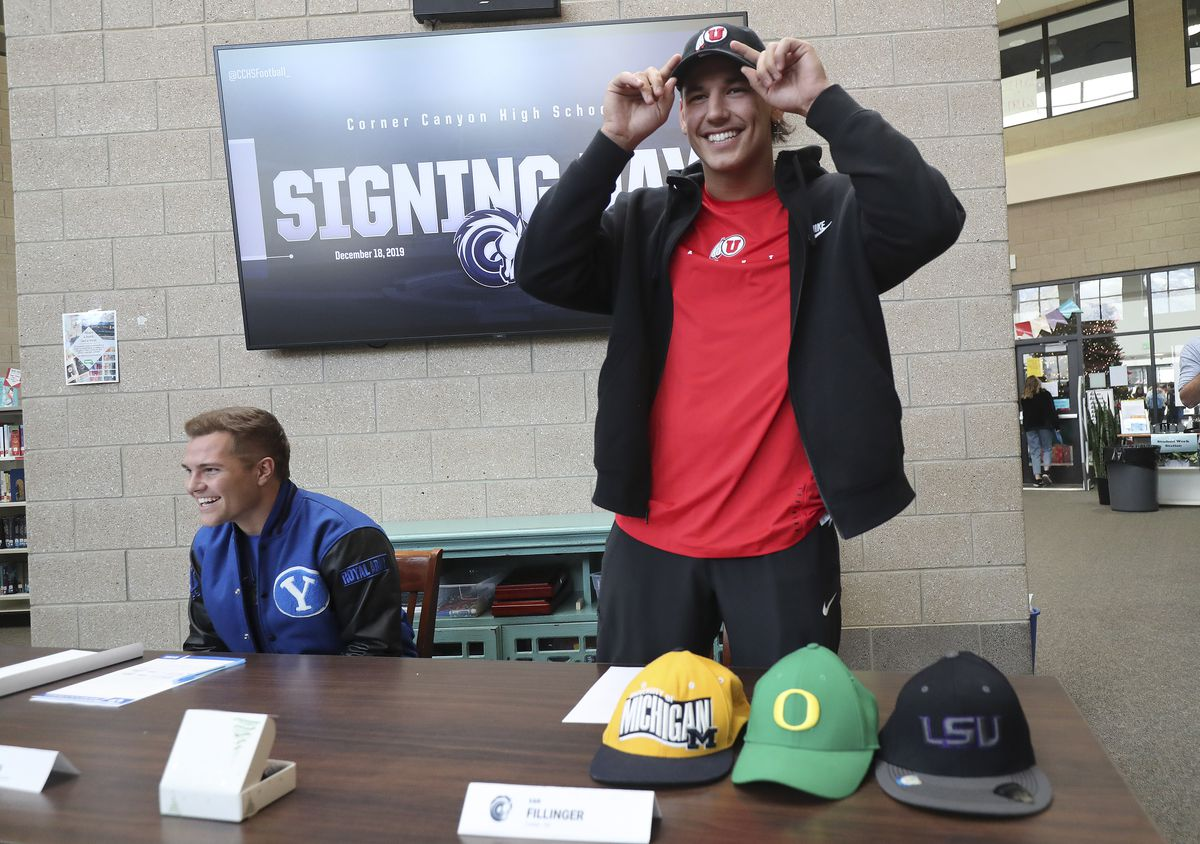 Corner Canyon High School athlete Van Fillinger, right, puts on a Utah hat and Josh Wilson wears a BYU jacket as they sign their National Letters of Intent in Draper, Utah, on Wednesday, Dec. 18, 2019. Fillinger signed with Utah and Wilson signed with BYU.