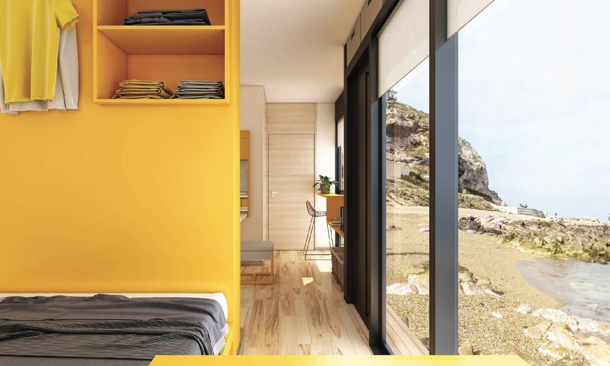 Bedroom with wall of windows and yellow paint