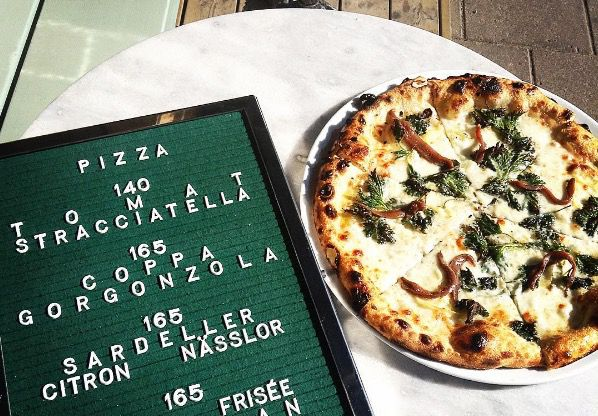 A whole pizza next to a hand-lettered menu on a small marble table