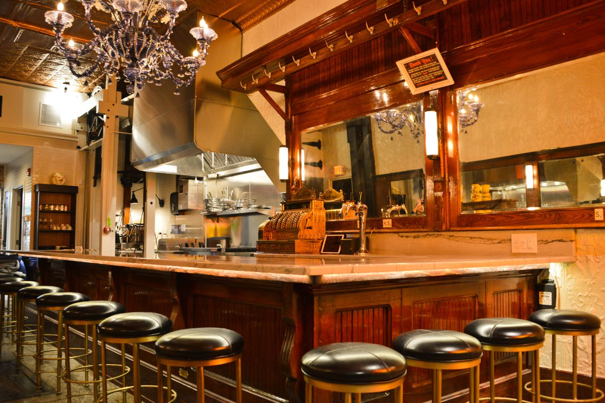 old looking restaurant with counter, stools, chandelier, and mirrors