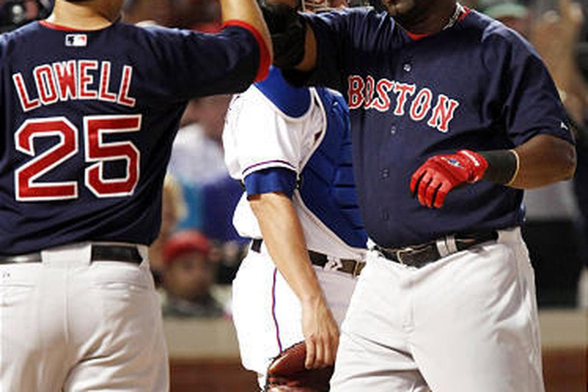 Boston Red Sox's David Ortiz, right, is congratulated by teammate Mike Lowell (25) after hitting a two-run home run in the sixth inning against the Texas Rangers.