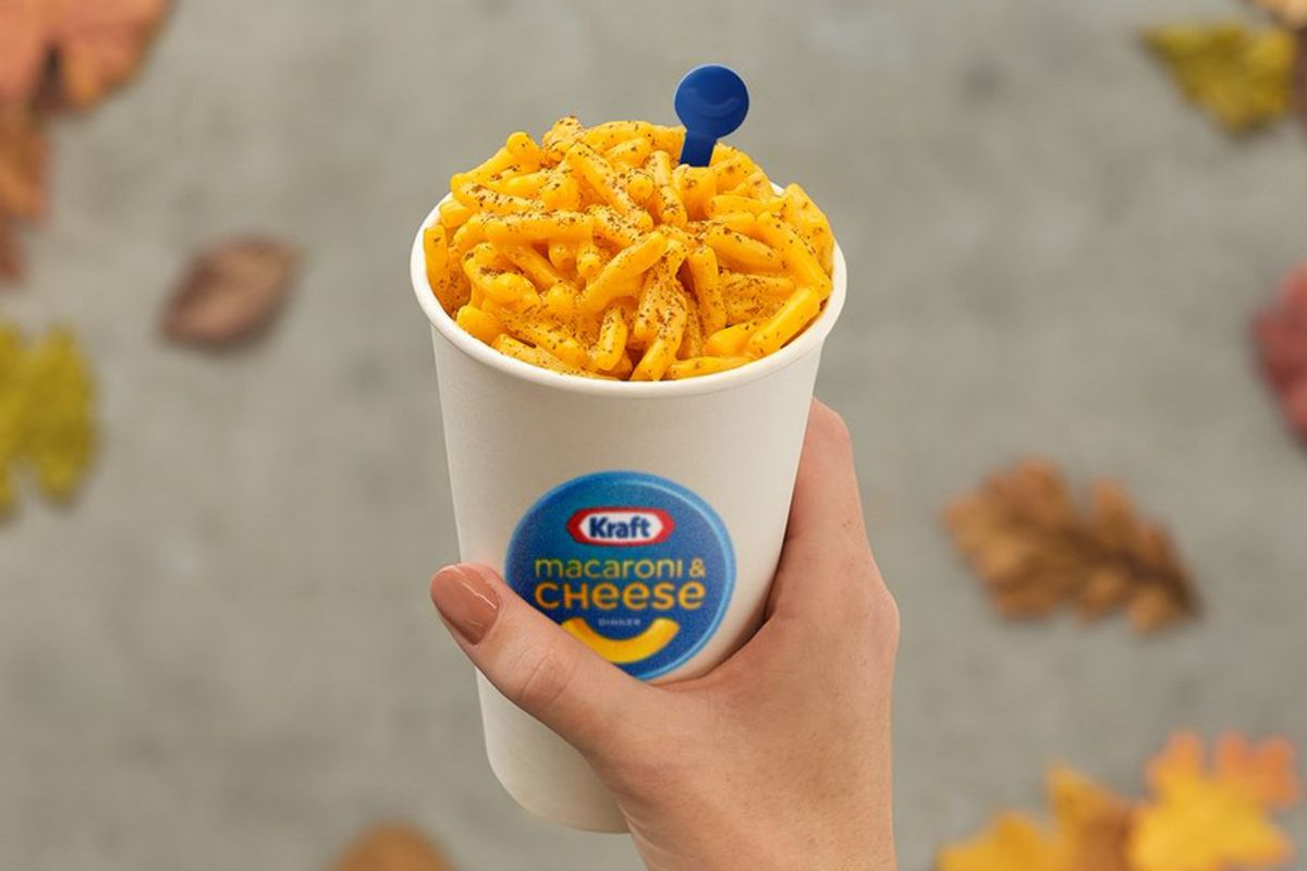 Cup of Kraft mac and cheese held in hand.