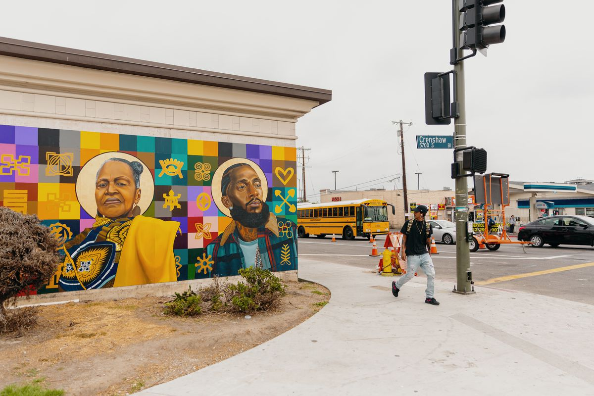 Corner of Crenshaw Blvd. A young man walks past a colorful mural of an older African American woman and a young African American man.