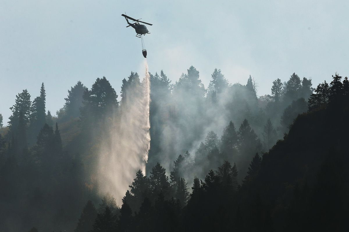 A helicopter drops water on the Pole Creek Fire in Woodland Hills on Friday, Sept. 21, 2018.