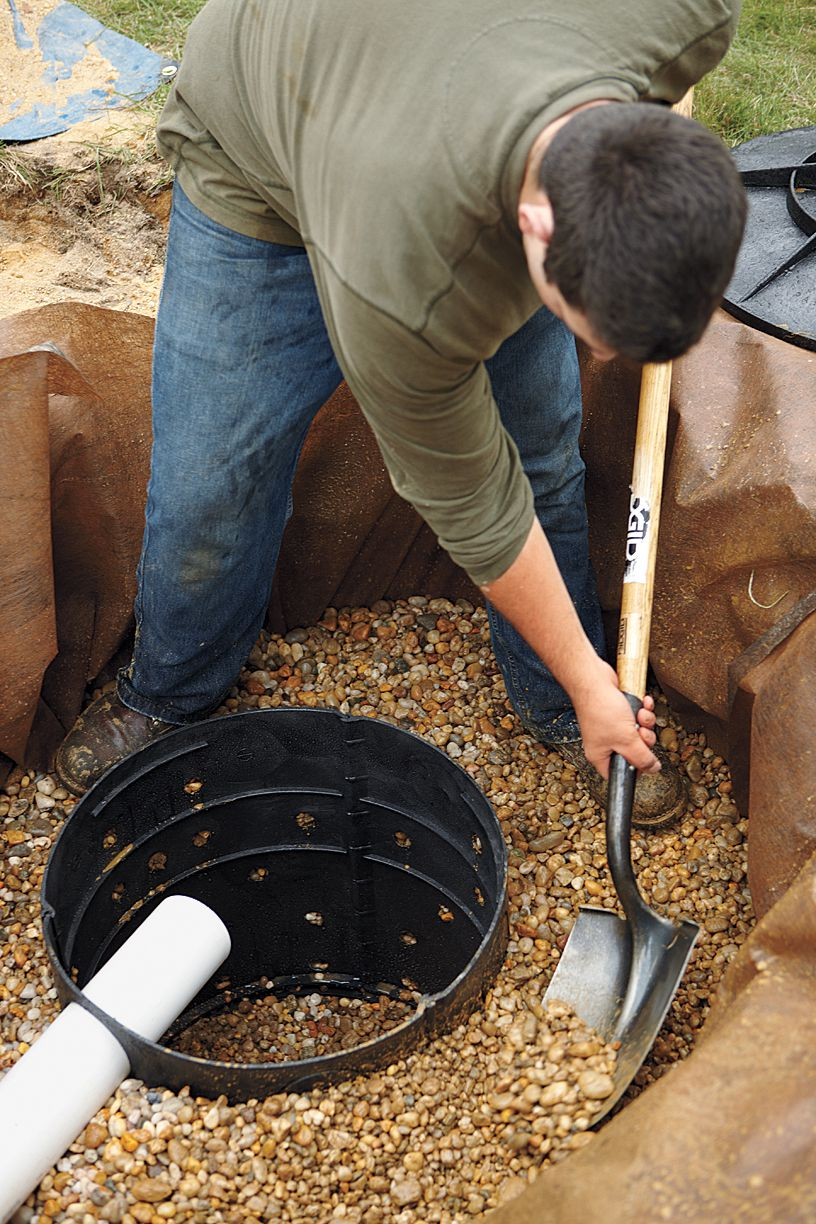 Man Shoveling Stone Into Dry Well