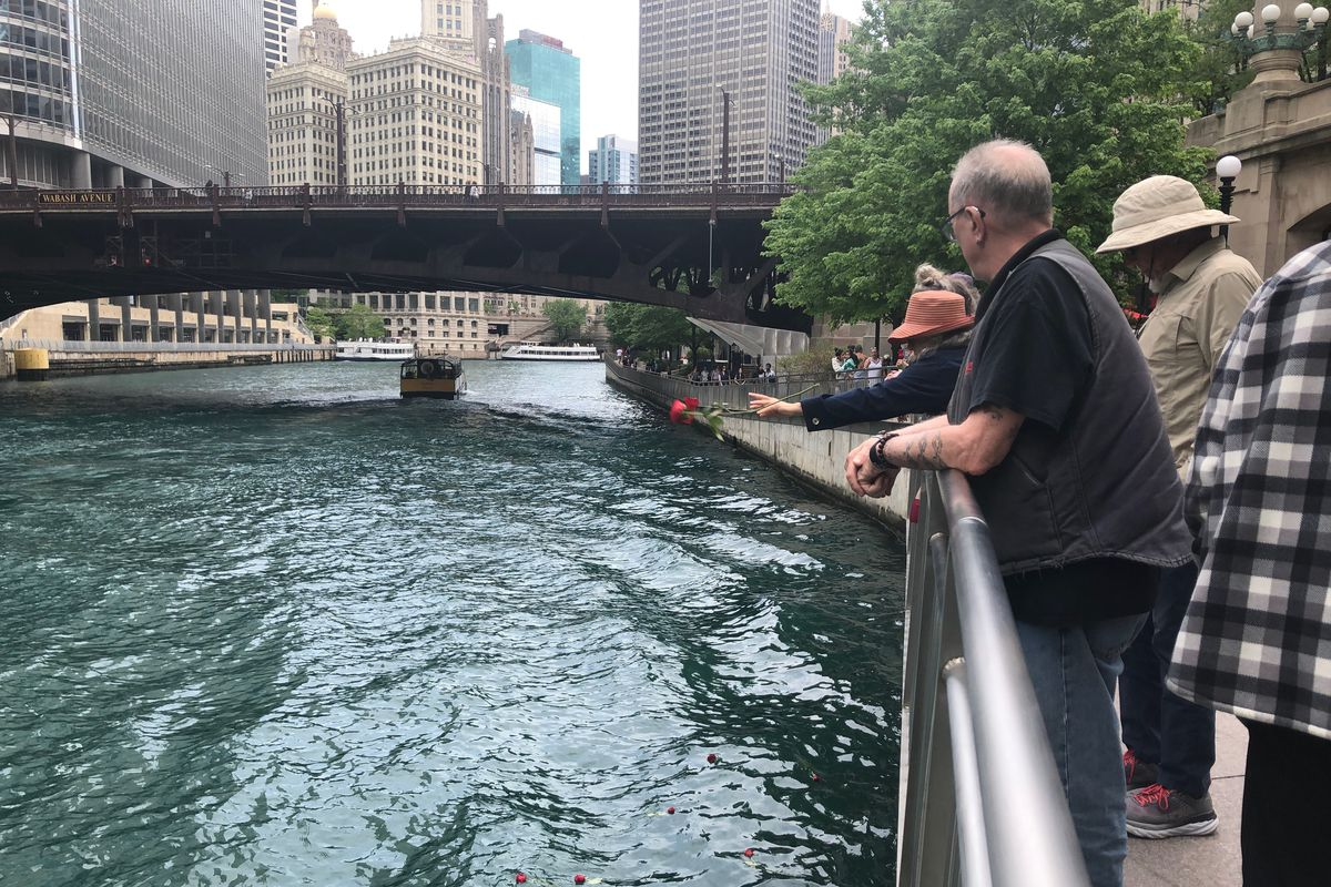 A woman throws a rose into the Chicago River