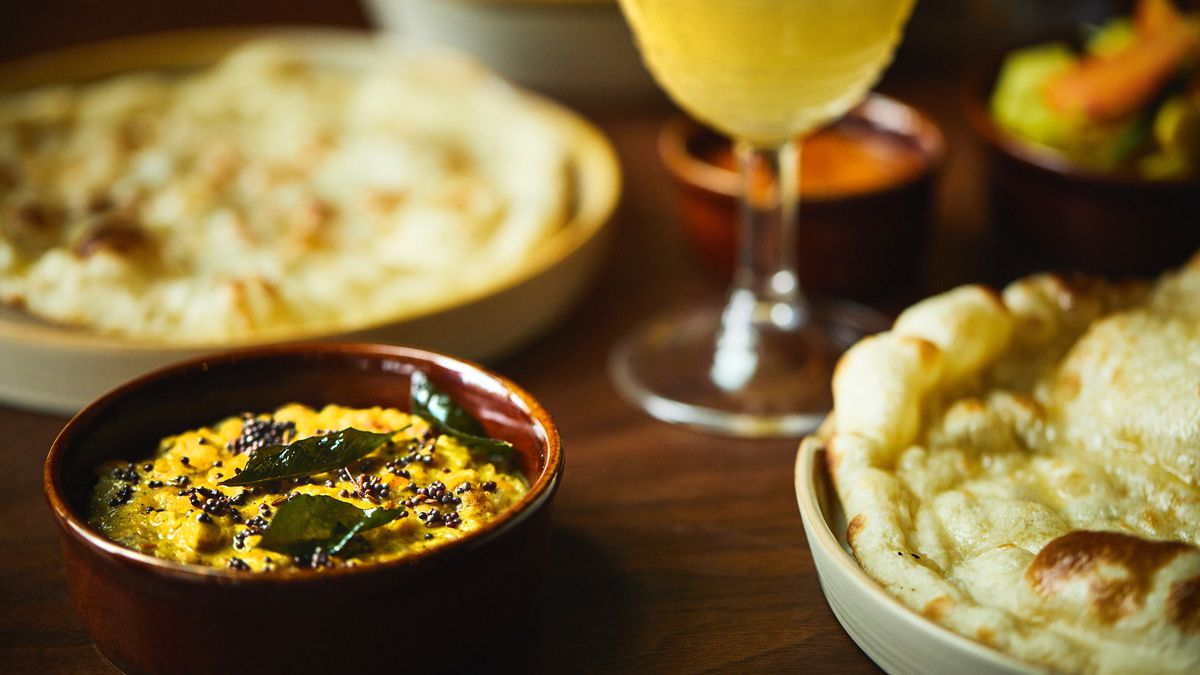 An assortment of Sri Lankan dishes, along with a yellow-colored cocktail.