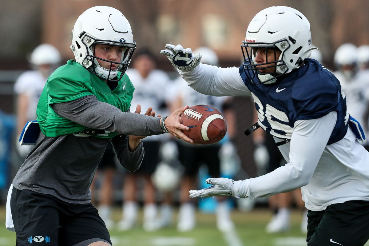 Quarterback Zach Wilson hands the ball off to running back Tyler Allgeier during BYU football practice in Provo on Friday, March 6, 2020.