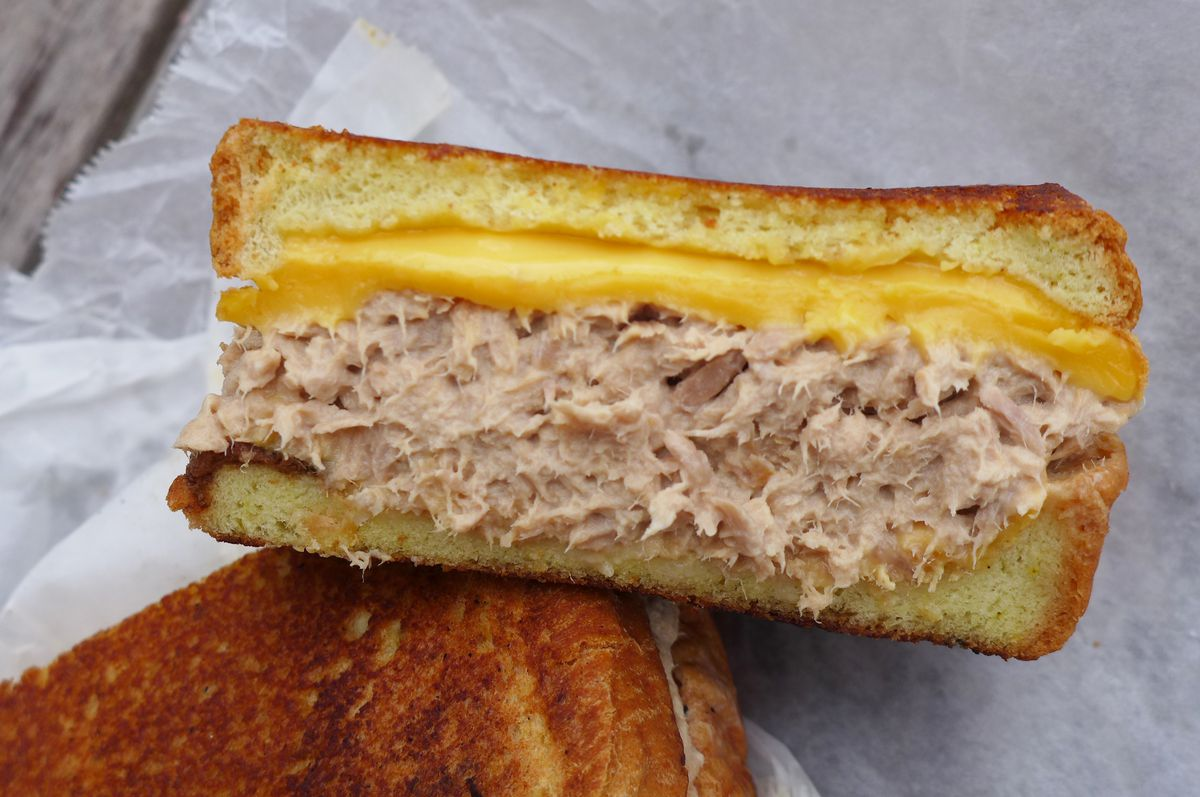 A tuna melt split open to reveal tuna and melted cheese.