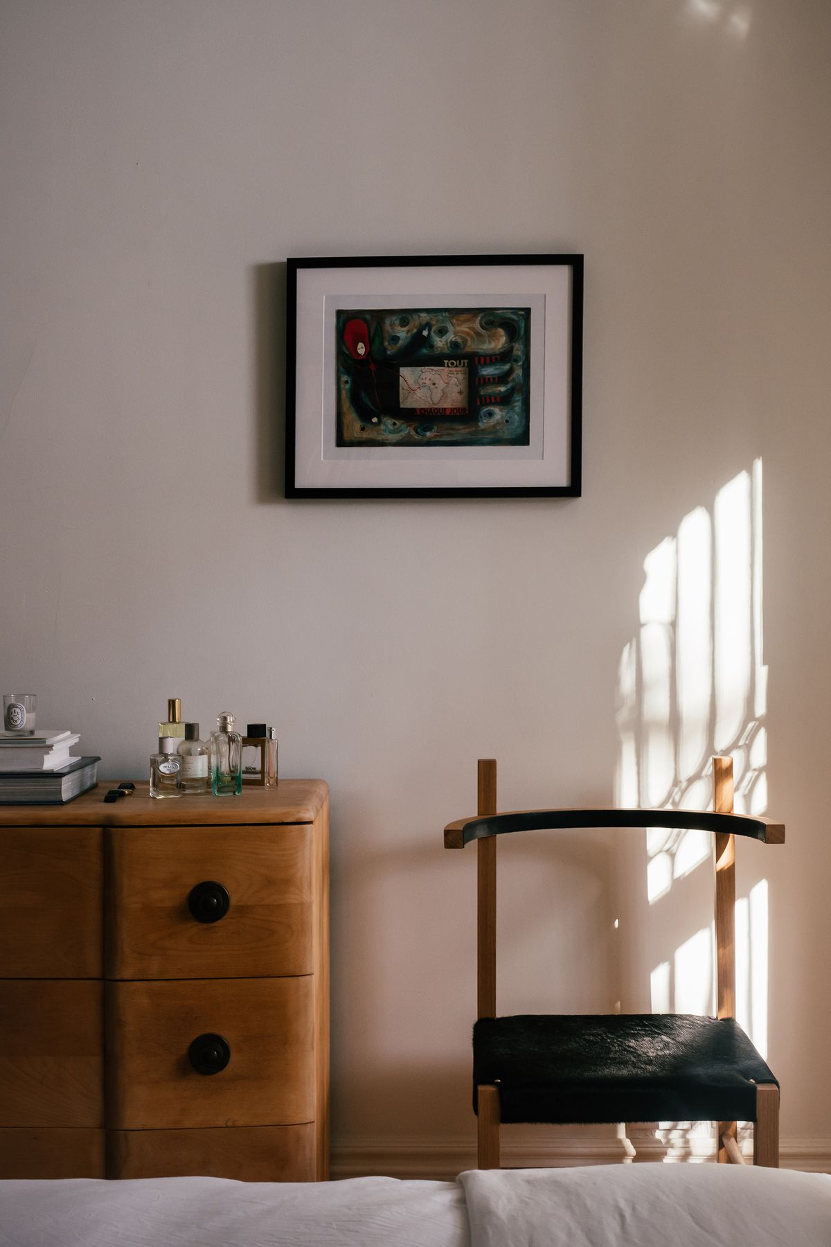 A modern chair with a curved back sits next to a vintage chest of drawers.