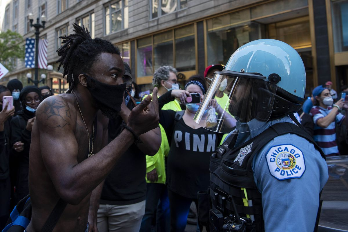 A protester gets into a police officers face and flips him off during a protest for the death of George Floyd, Saturday, May 30, 2020.