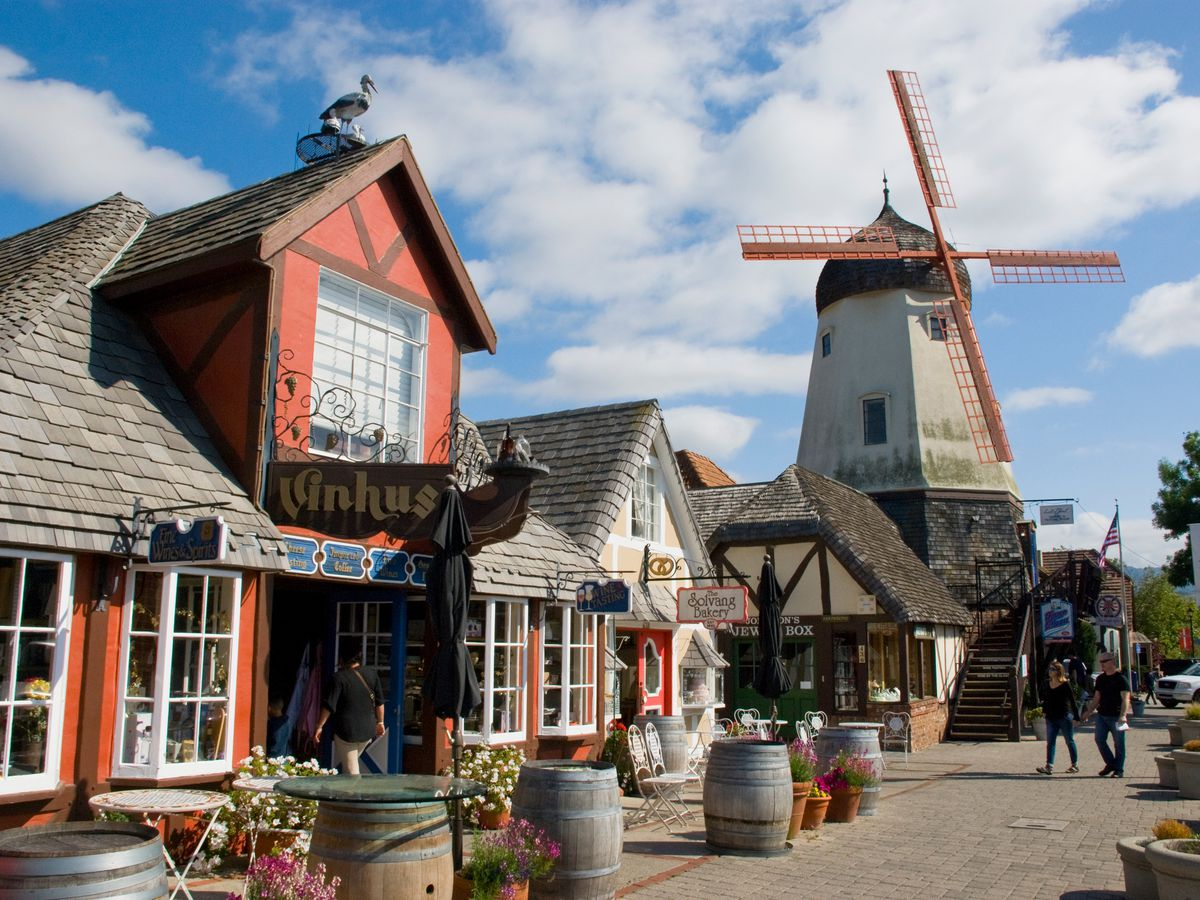 A row of shops in buildings with bay windows and gable roofs; a tall windmill stands in the background.