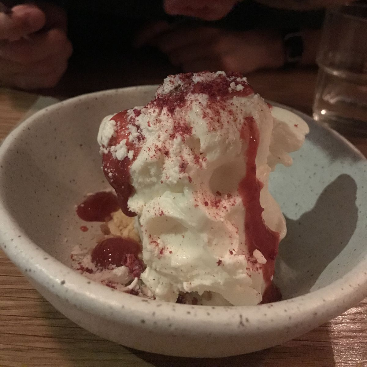 A scoop of mascarpone gelato is topped with berries in a speckled bowl