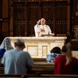 Very Rev. Martin Diaz prepares to offer communion to those attending Mass at the Cathedral of the Madeleine on Tuesday, May 12, 2020.