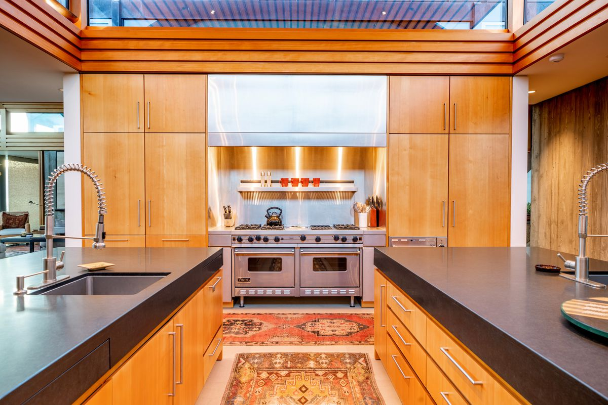 A wood kitchen with black countertops and a stainless steel chefs stove.