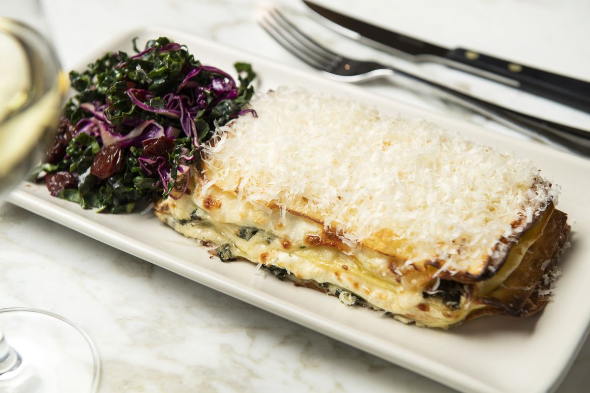 A white rectangular plate holds a slab of lasagna, and salad made with kale on the other side.