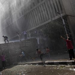 Egyptian security forces, not shown, use a water cannon against protesters climbing cement blocks closing the street that leads to the U.S. embassy during clashes in Cairo, Egypt, Friday, Sept. 14, 2012. The protests are part of widespread anger across the Muslim world about a film ridiculing Islam's Prophet Muhammad.
