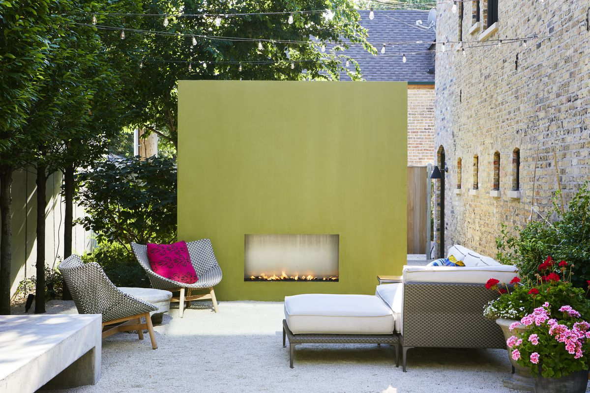 An outdoor area featuring an avocado wall with a fireplace and seating nearby.