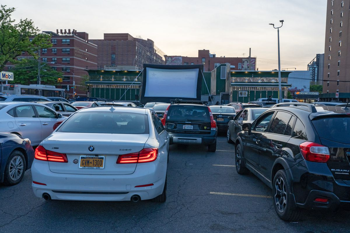 Cars are lined up behind each other in a drive-in movie theater with a large projection screen up front