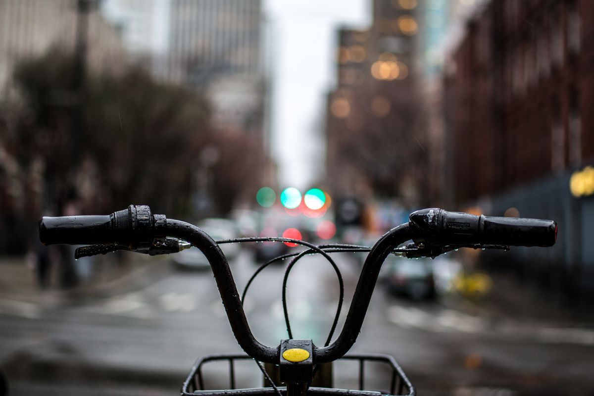 The handlebars of a bike in the foreground, and the rider is clearly looking at a rainy street.