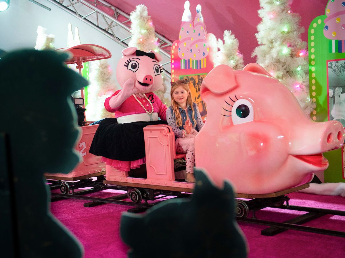 A group of pink pigs with holiday decorations and lights are on display at Macy's in Atlanta.