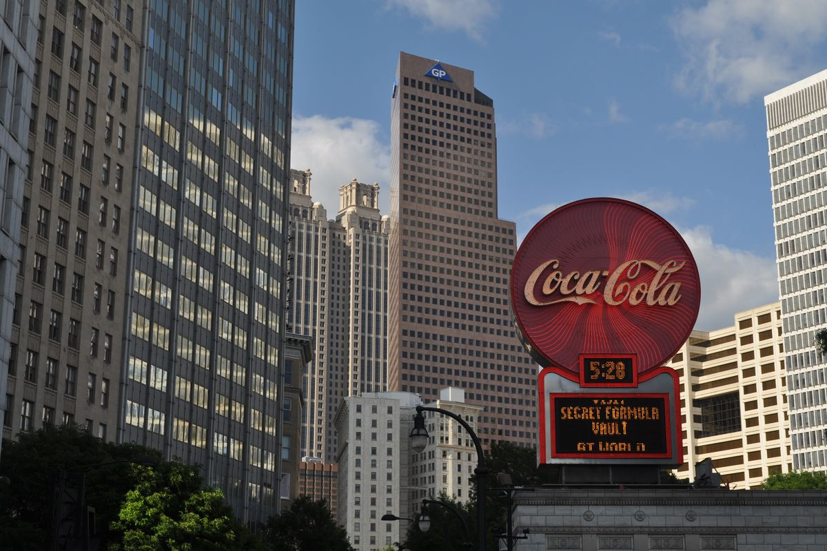 A view of the Coca-Cola sign atop the Olympia Building, with skyscrapers rising behind.