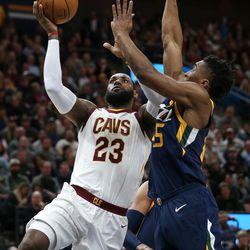 Cleveland Cavaliers forward LeBron James (23) lays it up ahead of Utah Jazz guard Donovan Mitchell (45) at Vivint Arena in Salt Lake City on Saturday, Dec. 30, 2017.