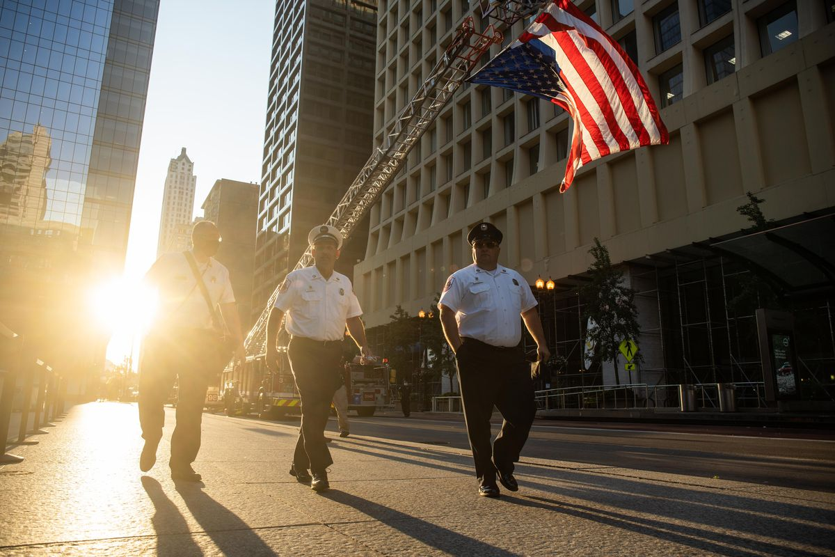 Members of the Chicago Fire Department walk past two fire trucks hoisting an American flag during the commemoration of the 20th anniversary of 9/11.