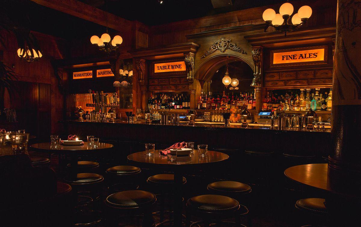 A dark tavern space with a bar.