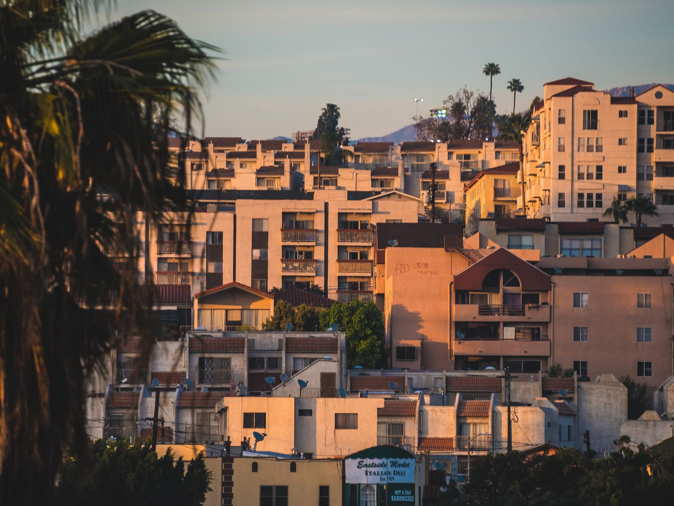 A cluster of dense white and beige apartments on a hillside at sunset.