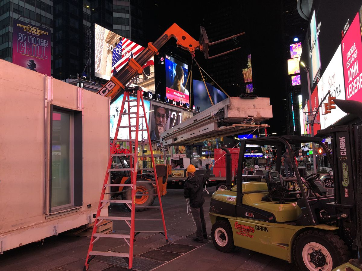A construction vehicle in Times Square is holding building materials. In the background are the brightly lit billboards on the buildings.