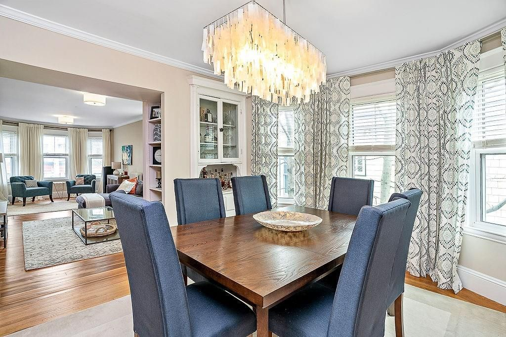 A sunny dining room with a table and chairs.