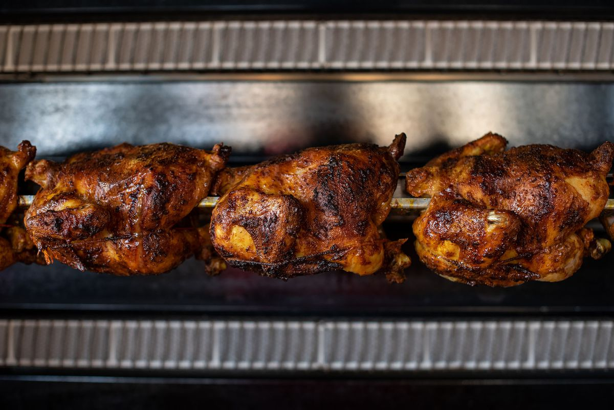 A line of rotisserie chickens that have just been cooked still hang on their bar.