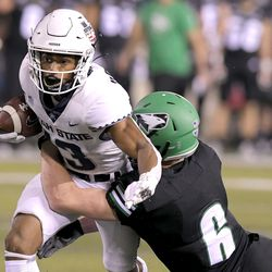 Utah State wide receiver Deven Thompkins (13) is tackled by North Dakota defensive back Evan Holm (6) during the first half of an NCAA college football game Friday, Sept. 10, 2021, in Logan, Utah.