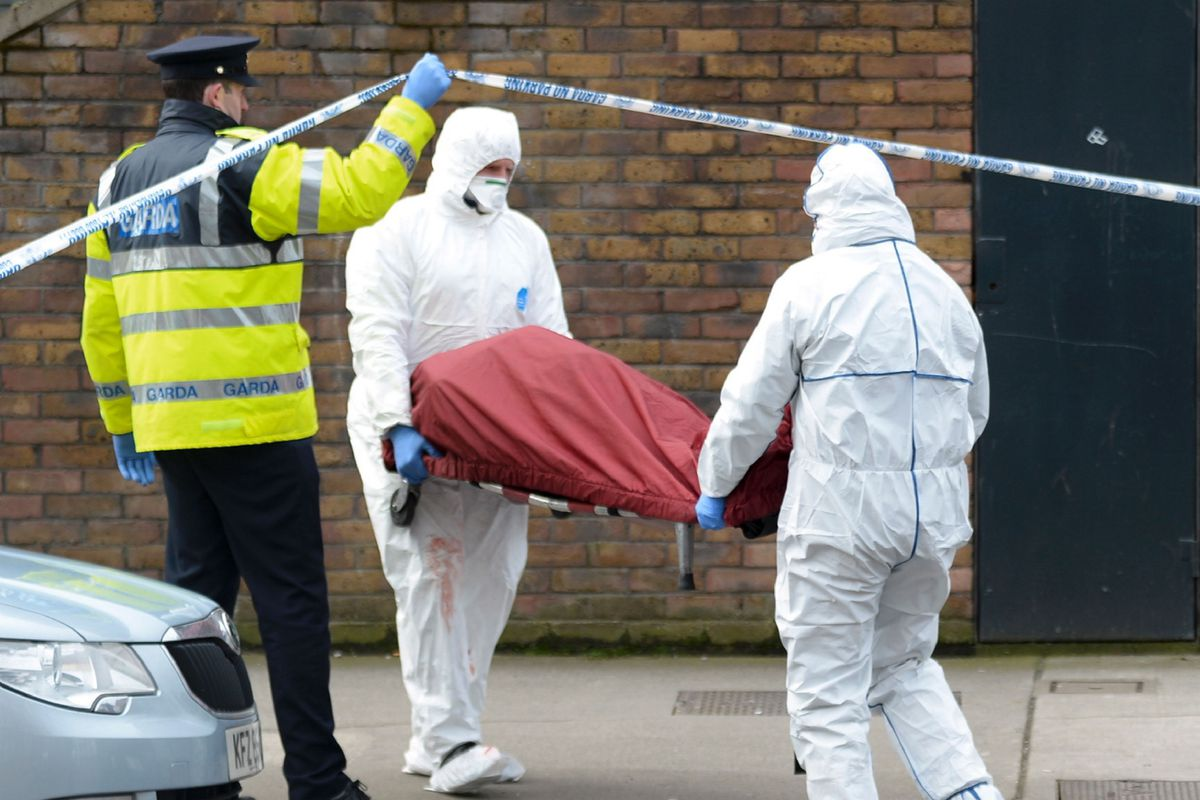 Members of the Irish emergency services carry a gurney taken from a residential address that was the scene of a fatal shooting and put it into an ambulance in Dublin on February 9, 2016. A man was shot dead in Dublin on February 8, Irish police said, in a suspected gangland reprisal attack for a fatal shooting at a boxing event last week.