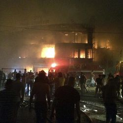 Iraqi firefighters try to extinguish a fire as civilians gather after a car bomb at a commercial area in Karada neighborhood, Baghdad, Iraq, early Sunday, July 3, 2016. Bombs went off early Sunday in two crowded commercial areas in Baghdad.
