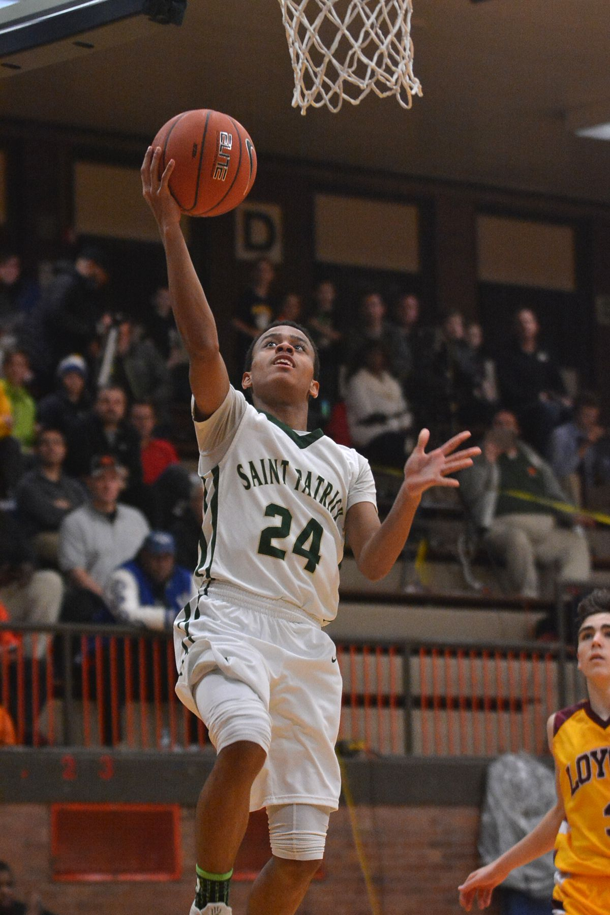 St. Patrick's Laurence Merritt (24) gets a steal and drives straight to the basket against Loyola in 2017.