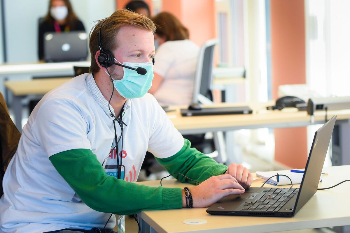 A person in a face mask and telephone headset sits at a laptop computer.