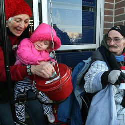 Doug Holladay, a former Salvation Army worker who is fighting terminal lung cancer, rings a bell for donations a final time in Riverdale, Thursday, Dec. 5, 2013. Doug's mother, Dorothy Holladay, helps Eliza Larsen place donations in the pot.