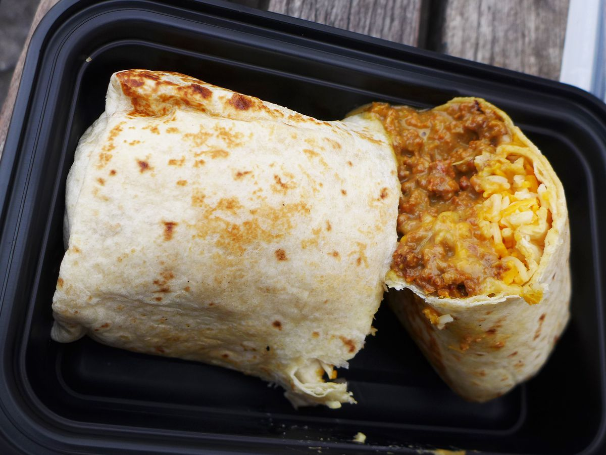 Two halves of a burrito are filled with beans, rice, and cheese in a black takeout tray