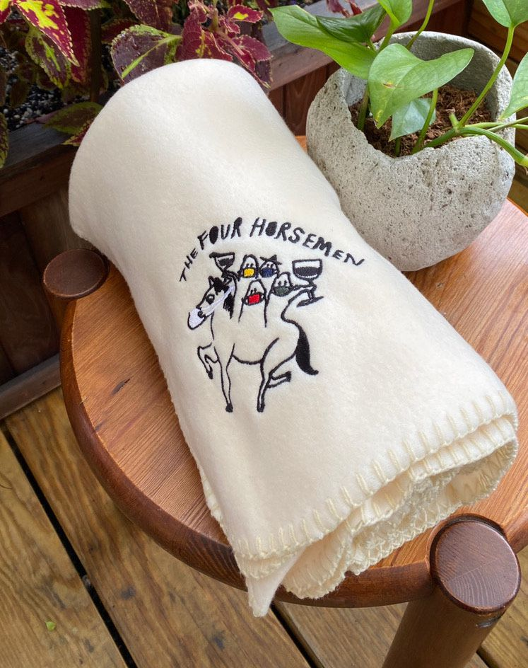 """A cream blanket with the words """"the Four Horsemen"""" and a colorful hand-drawn logo rests on top of a wooden side table"""