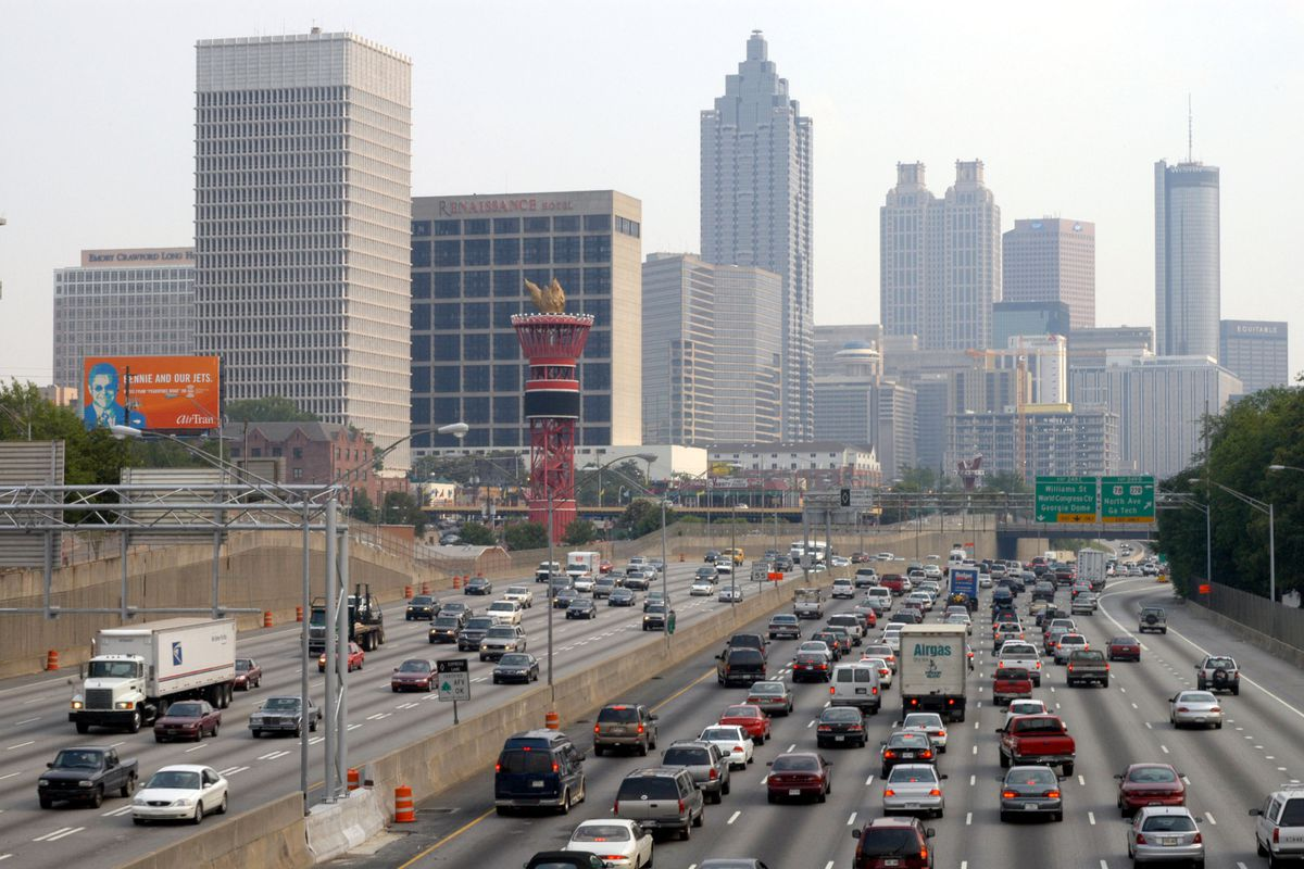 A picture of atlanta traffic, with cars in the foreground and buildings behind.