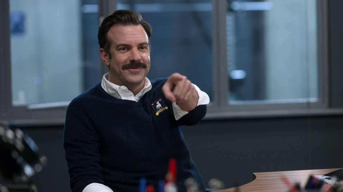 Jason Sudeikis grins and points into the camera in Ted Lasso
